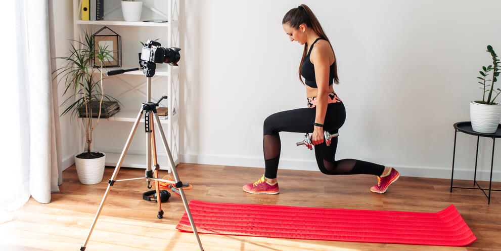 Fitness instructor filming a video workout at home in front of a camera on a tripod