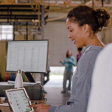 Woman in fitness studio checking in at the front desk using an iPad