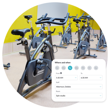 Spin class equipment and screen showing check out of date, time, room, and staff member