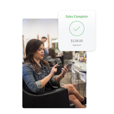 Client in salon chair using mobile device to complete salon transaction