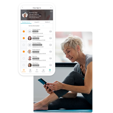 Instructor using her phone to view client profiles signed up for yoga class